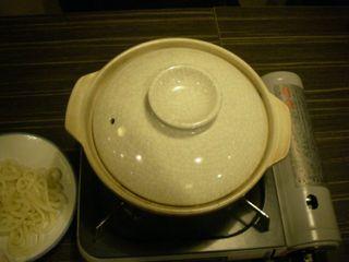 鍋に蓋をして加熱。脇にはうどんが用意されている。